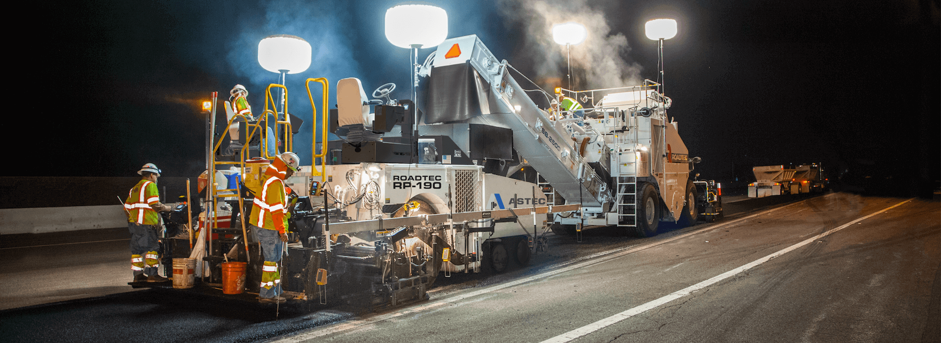 Roadtec RP-190 highway class asphalt paver paving at night with a Roadtec Shuttle Buggy Material Transfer Vehicle
