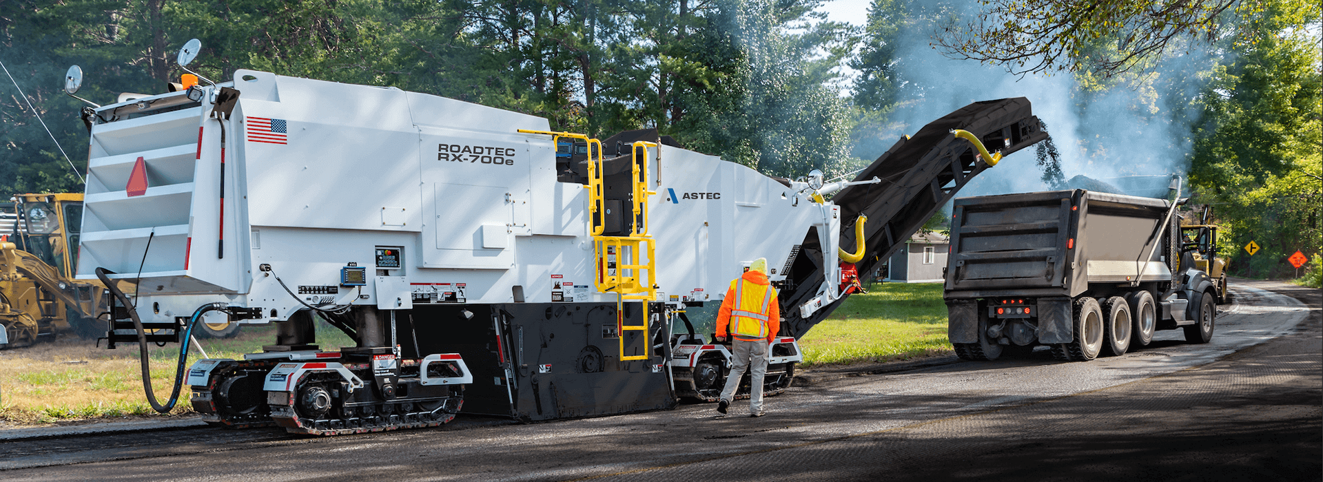 Roadtec RX-700 cold planer milling asphalt off the road surface into a dump truck