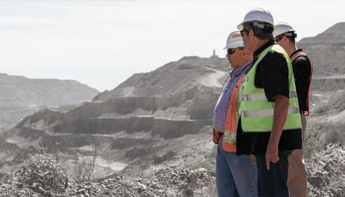 Three men overlooking a quarry