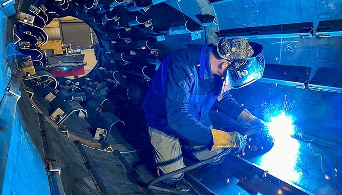 Welder inside of an asphalt drum welding flights
