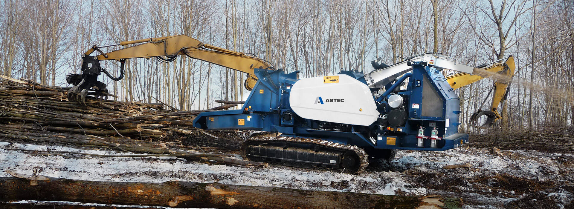 Peterson 4310B Highwalker Drum Chipper land clearing a right-of-way in the snow.
