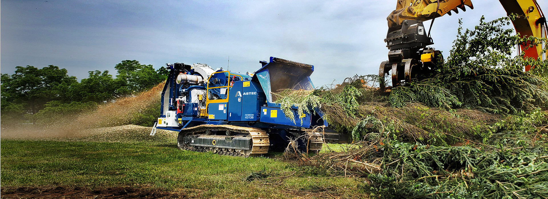 Peterson 4310B Drum Chipper chipping whole trees making microchips and being loaded by a grapple excavator