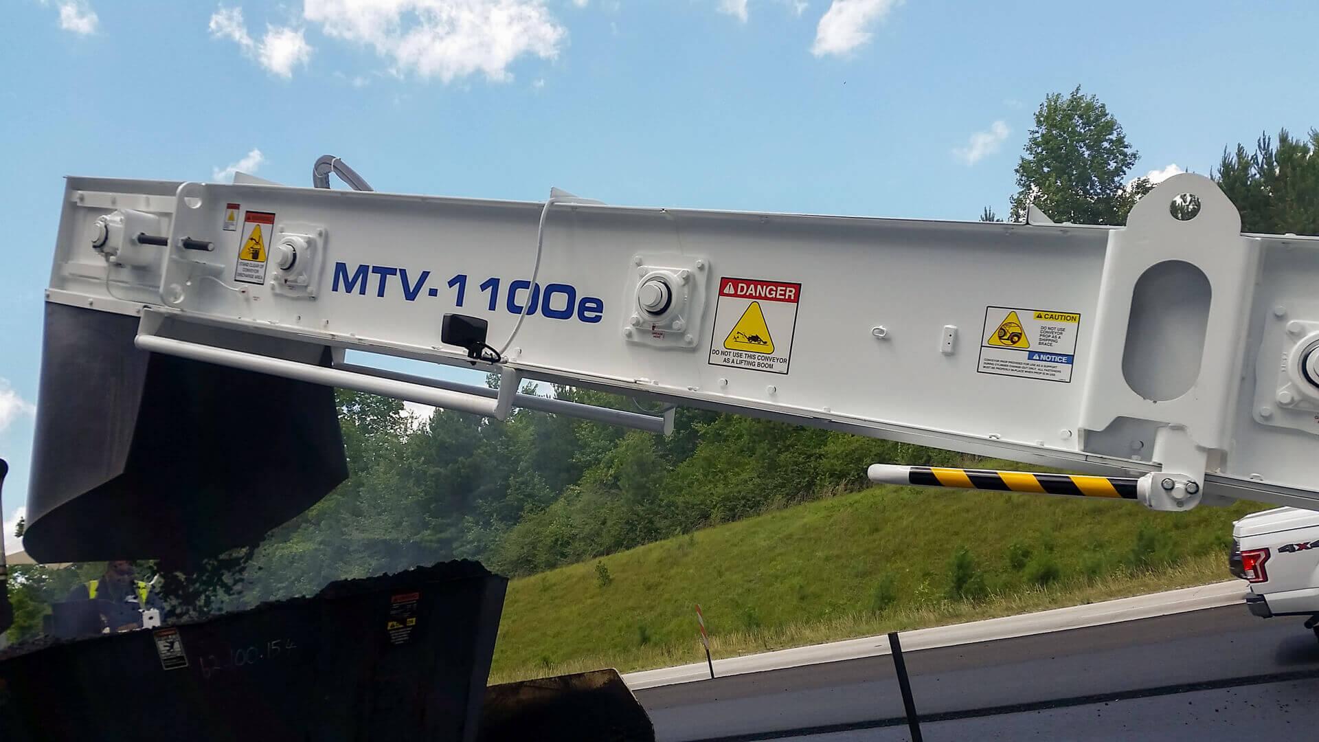 Roadtec MTV-1100 Material Transfer Vehicle conveyor putting material into a Roadtec paver hopper