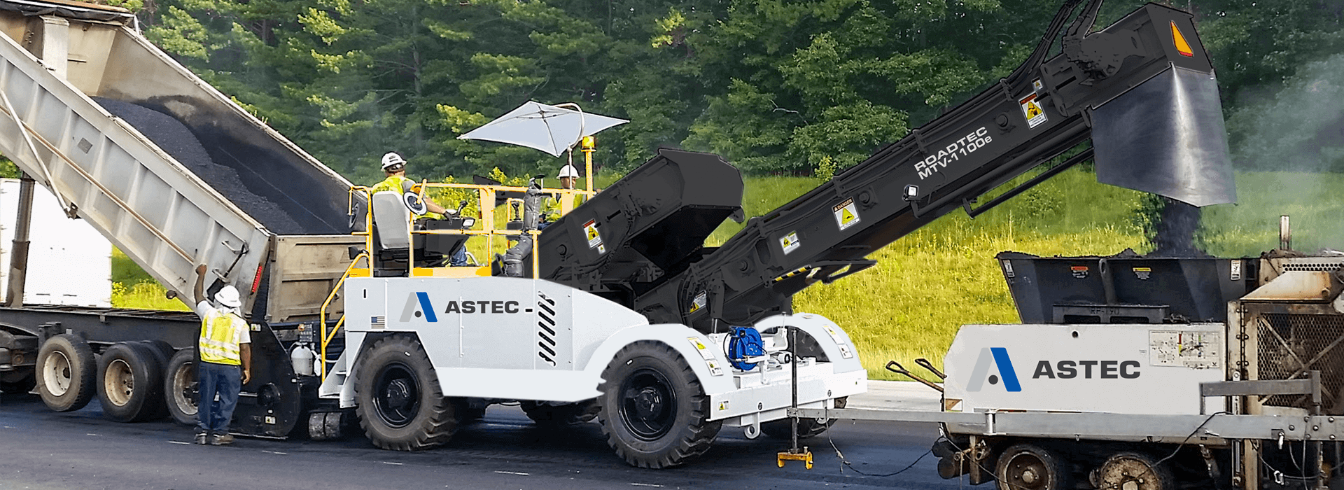 A Roadtec MTV-1100 material transfer vehicle working with a roadtec paver
