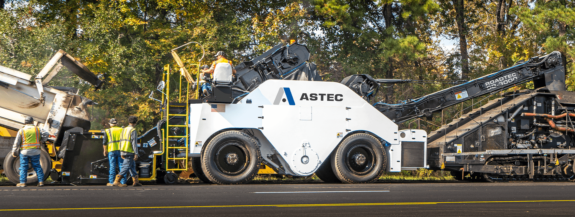 Roadtec SB-3000 Shuttle Buggy Material Transfer Vehicle paving with a Spray Paver