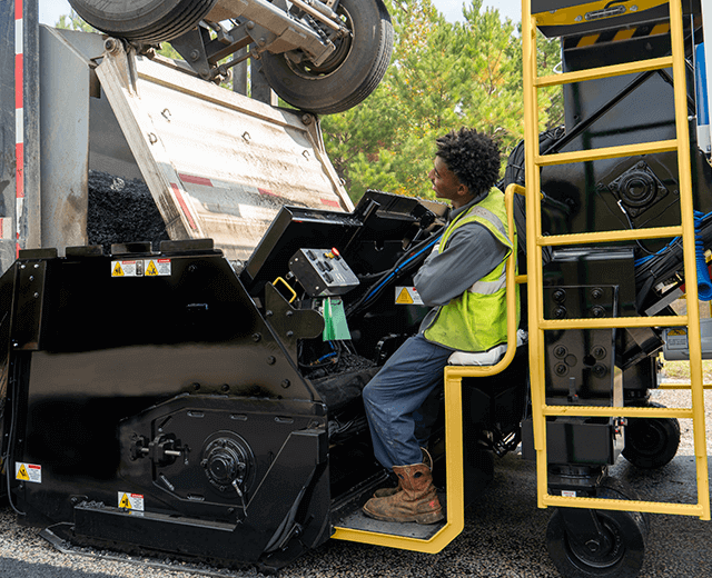 A Roadtec SB-3000 Shuttle Buggy Material Transfer Vehicle working as a dump truck unloads asphalt into the hopper with a ground crew memember sitting down at the ground control station