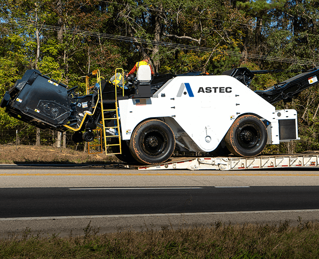 The Roadtec SB-3000 Shuttle Buggy MTV being loaded onto a lowboy trailer