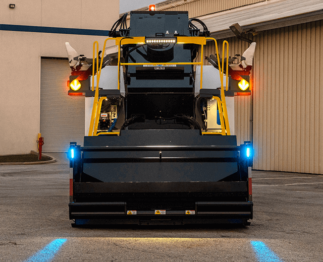 The Roadtec SB-3000 Shuttle Buggy Material Transfer Vehicle showing the front projectors that display blue lines on the ground that serve as guides for trucks