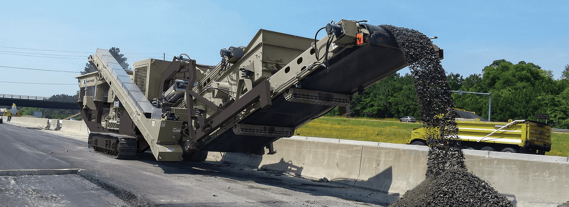 Mobile track-mounted impactor crushing and recycling asphalt from a highway.