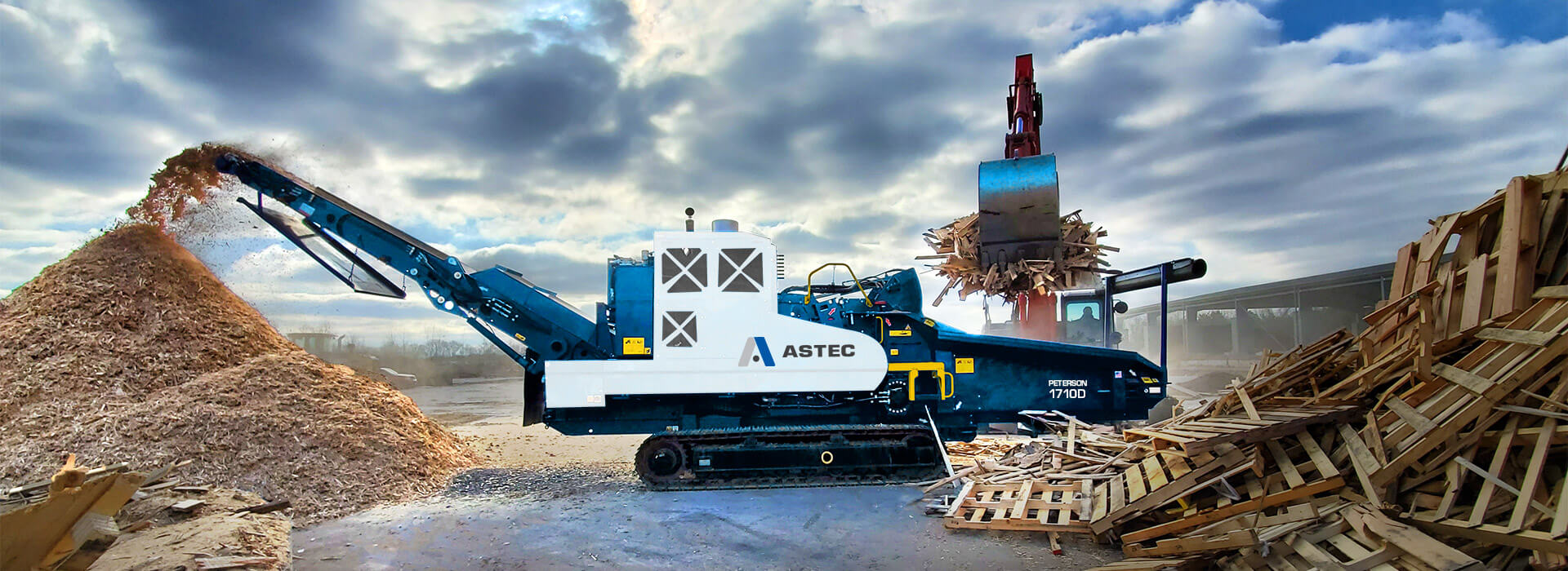 An Astec Peterson 1710D Horizontal Grinder recycling pallets into mulch and being loaded with an excavator.