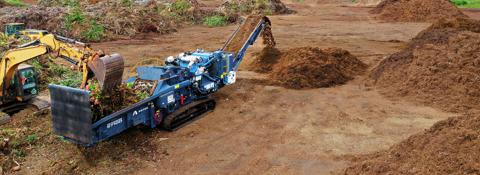 Astec Peterson 5710D Horizontal Grinder making compost from green waste in Hawaii with an loading excavator.