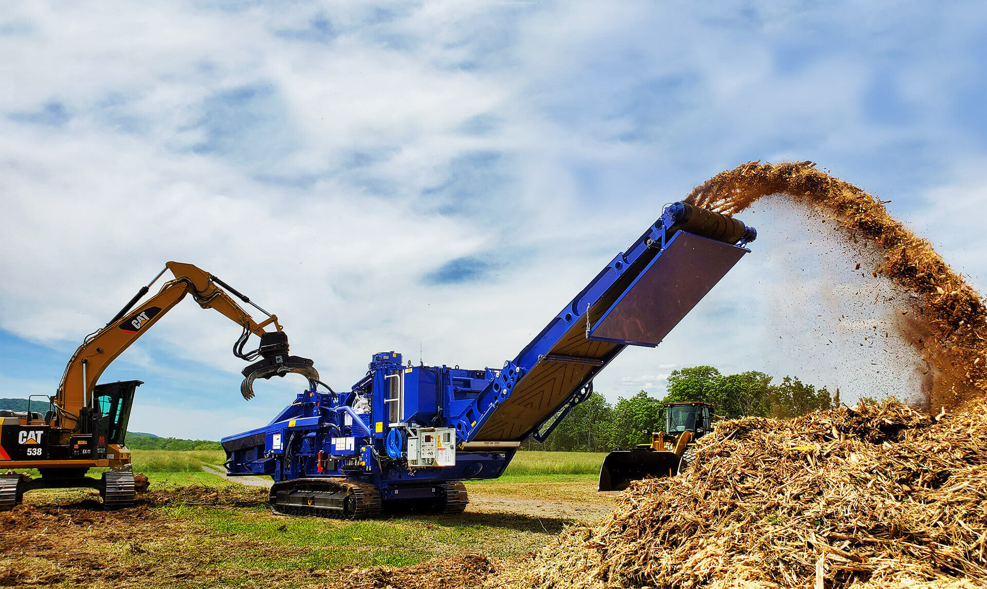 Astec Peterson 5710D Horizontal Grinder making biomass in Pennsylvania with a grapple loading excavator.