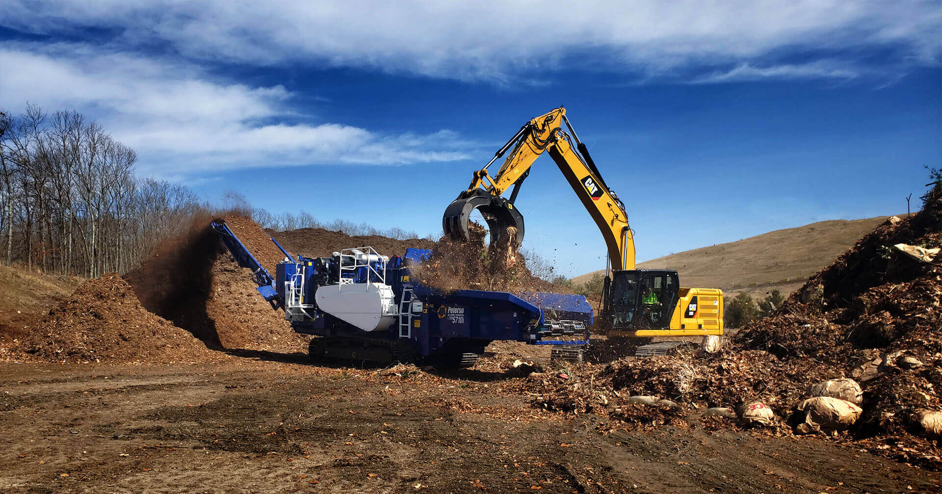 Astec Peterson 5710D Horizontal Grinder making compost from bags of leaves with a excavator loader