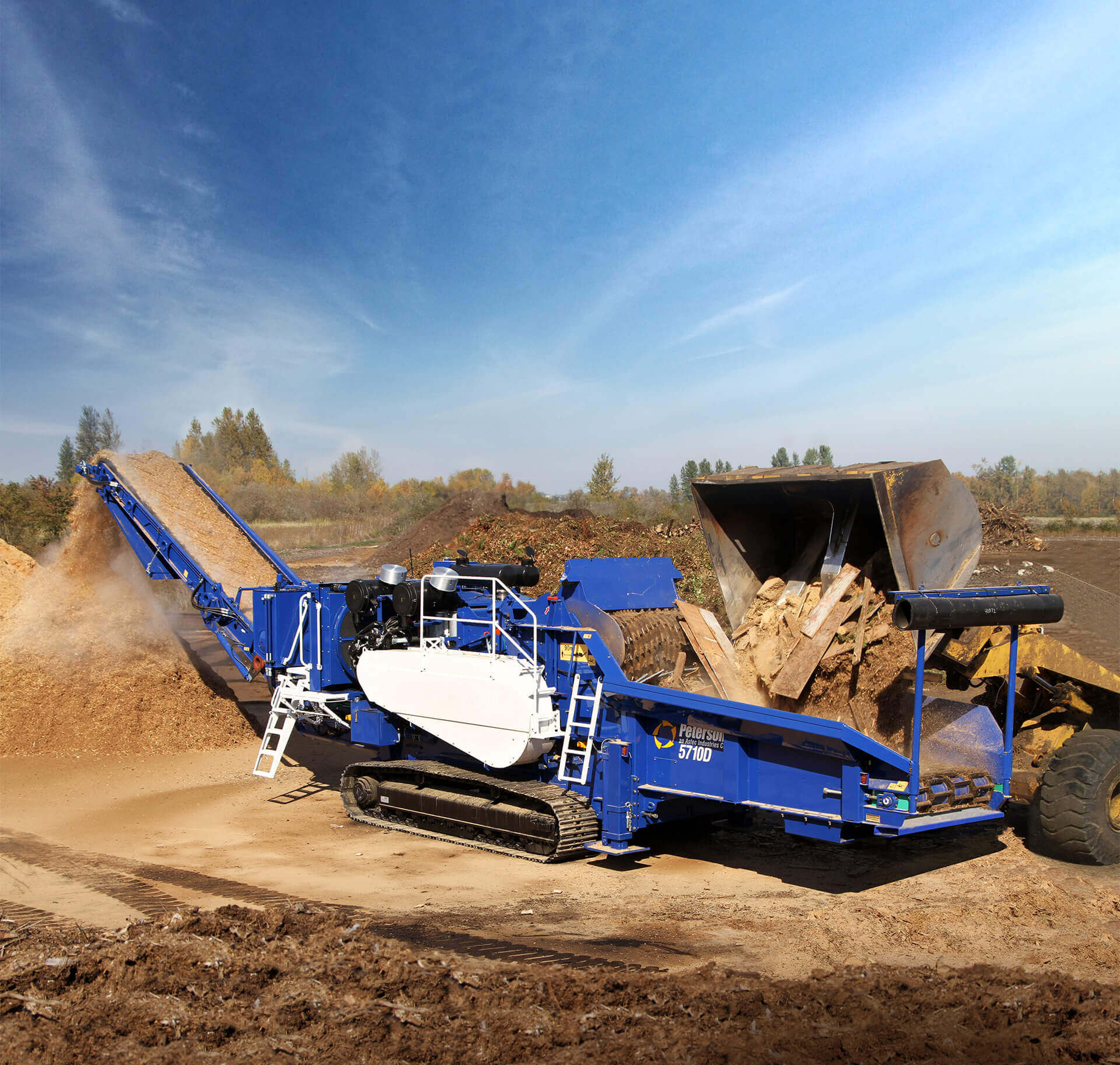 Astec Peterson Horizontal Grinder making mulch from scrap lumber and wood waste while being loaded by a front end loader.