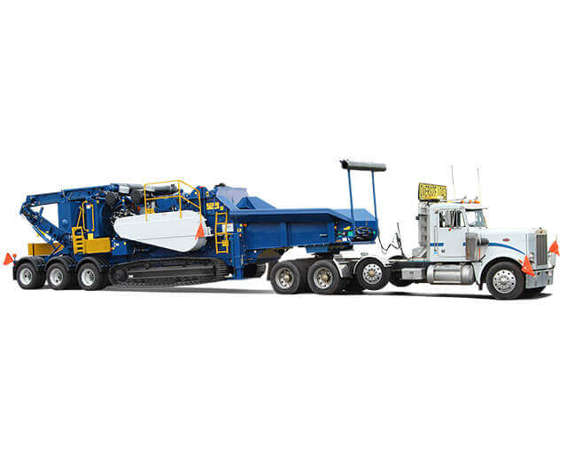 An Astec Peterson tracked horizontal grinder being transported with a semi and a tow dolly.