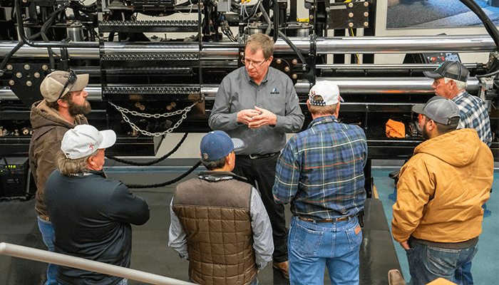 A group of adult students learning from an instructor about pavers.